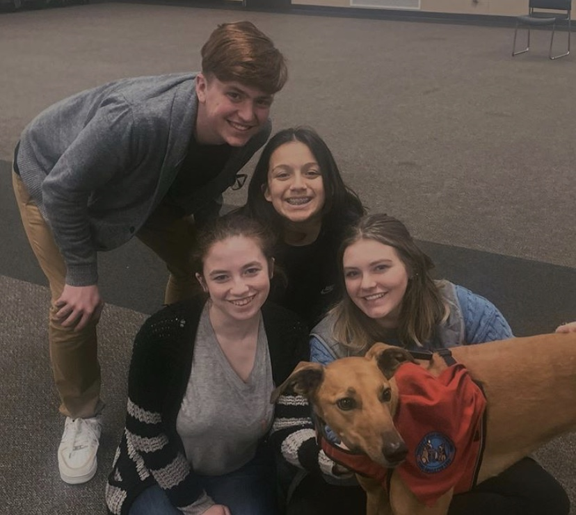Owen Clark, '21, Haven Noll, '20, Olivia Shank, '21, and Nina Goodwin, '20 pose with therapy dog, Karly.
