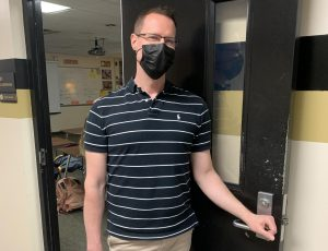 Señor Johnson waiting outside his classroom for class to start.