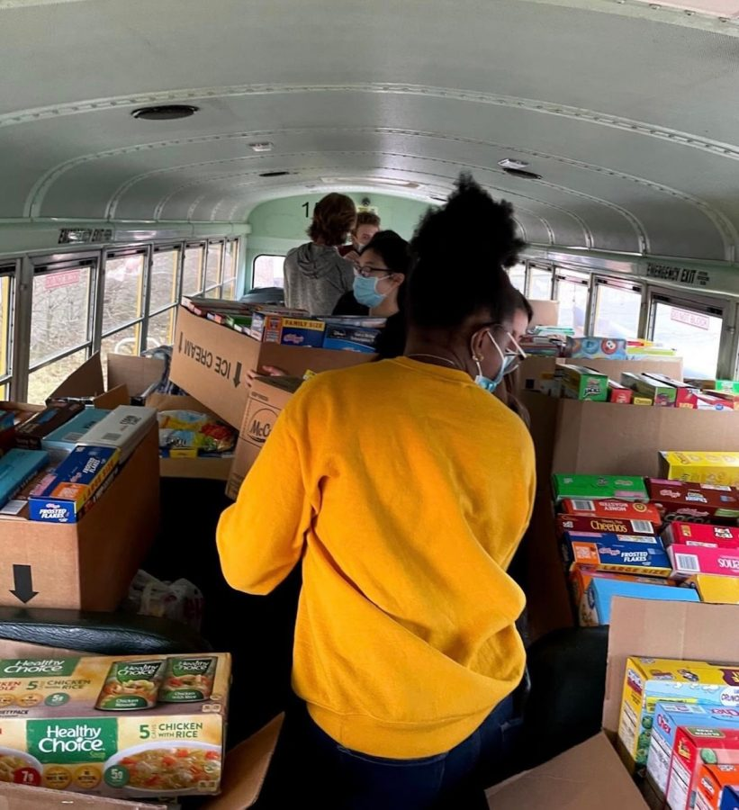 Students from Mrs. Houghs leadership class spend class time filling the bus with food donations.